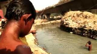 getlinkyoutube.com-Young rag-pickers dive into dirty water to beat Delhi's heat