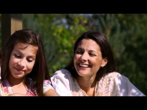 Close-up slow motion shot of a family in a beautiful garden on a bridge.