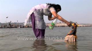 Woman in Salwar-kameez suit prays to statue in Ganges river