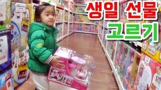 생일 선물을 사러 장난감 가게에 들린 여자 아기의 선물 고르는 모습