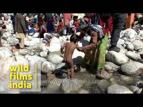 Mother bathing kid in freezing water of river Ganga at Gangotri