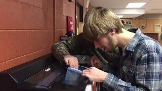 Students at Menomonie High School check trout eggs