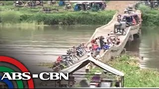 Isabela residents cross damaged bridge