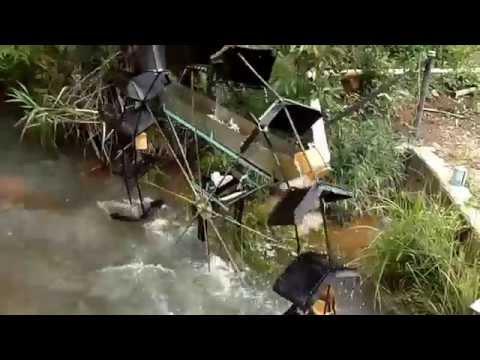 Roda d'agua movida pela correnteza do rio funcionando com rio cheio. Eleva a água