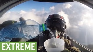 Fighter jet pilot drinks water cup while flying upside down width=