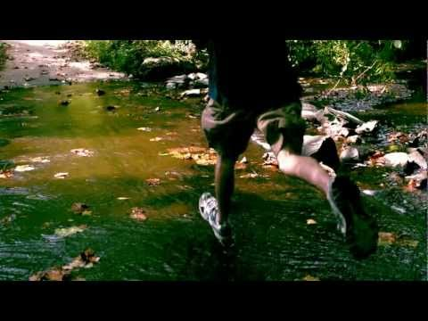 Slow Motion Runner Slow Mo View Running Jogging Through Water Flowing in Stream Creek Crossing Track