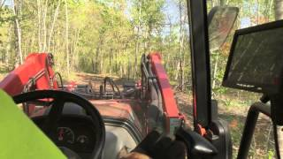 Kioti NX Series Tractor with a Wicked Root Grapple Working