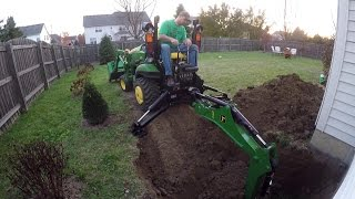 Compact Tractor Backhoe digs hole for basement egress window