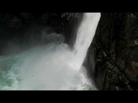 The waterfall pounds the lake at the pailon del diablo, banos, ecuador