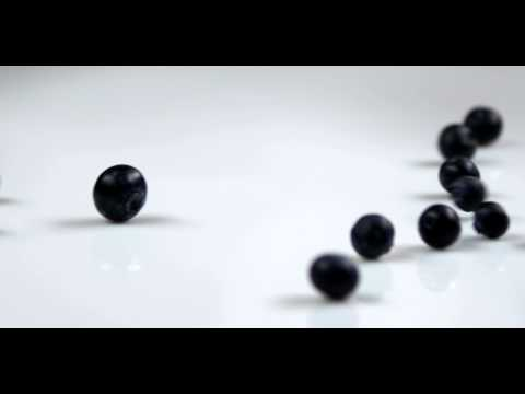 Royalty Free Stock Footage of Blueberries falling onto a table.