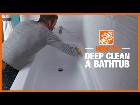 person cleaning bathtub with a rag