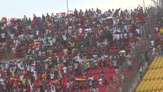Kotoko and Hearts supporters cheer  their teams in heavy rain