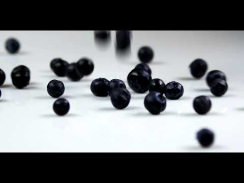 Royalty Free Stock Footage of Blueberries being dropped onto a table.