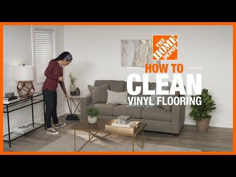 A man kneels on the floor to measure vinyl plank flooring