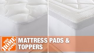 Quilted mattress pad on a bed.