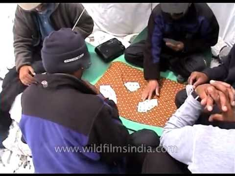Everest mountaineers play cards and listen to the radio, waiting for the weather to clear
