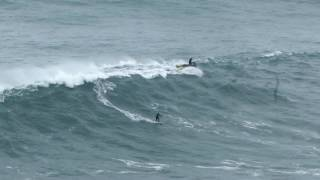 Nazare, Portugal - Nuno Santos surfing while playing the violin