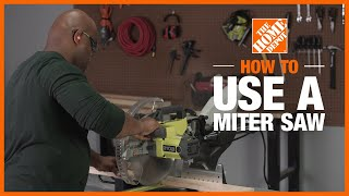 The blade of a power miter saw is lowered to cut a piece of crown moulding.