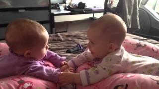 Tweeling babies houden elkaar voor het eerst vast