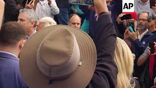 Stone leaves court waving peace sign to crowd