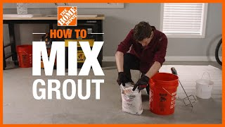 Man mixes grout with a margin trowel in a small bucket.