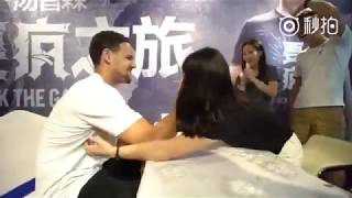 Klay Thompson plays arm wrestling against a female fan