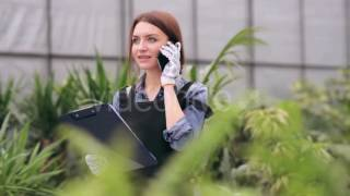 Female Gardener Talking On The Phone In Greenhouse - Stock Footage | VideoHive 15164224 width=