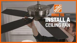A man installing a white ceiling fan.