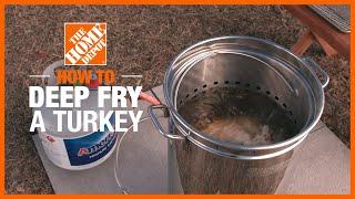 A fried turkey on a silver platter next to a gravy holder.