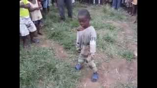 AN AFRICAN BOY DANCING IN THE VILLAGE