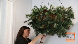 A hanging planter decorated with red ornaments, berry stems and poinsettias hangs in a room.
