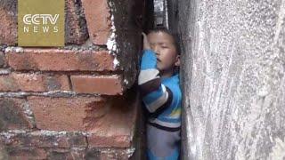 Naughty boy gets stuck between narrow walls