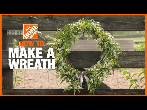 A video showing a woman making a wreath with greenery and a straw base.