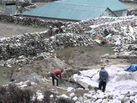 Everest Trek Nepal –  Local Masons breaking rock for building construction