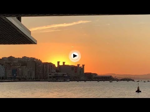 Los primeros rayos del sol y el ferry entrando en la bahía
