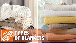 A stack of blankets and throws rest on a chair.