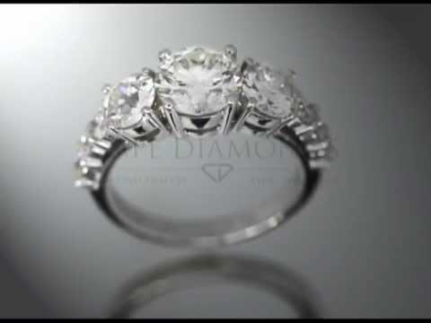 3stone,round diamond,4claws,3 small round diamonds a side,platinum,engagement ring