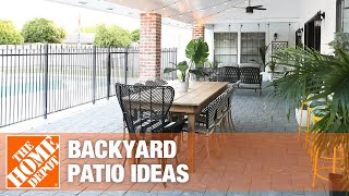 A small backyard patio featuring a loveseat, umbrella and outdoor coffee table.