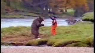 a man  fighting over a fish with bear