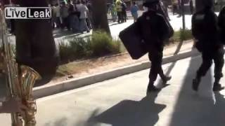 Sax guy provides riot police with suitable background music