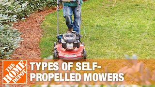 A woman in jeans and a tee shirt walks behind holding on to a self-propelled lawn mower over a grass yard.