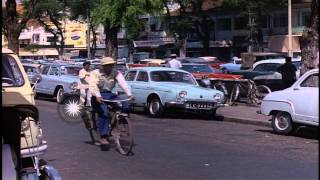 Vehicles move down a street and girls cross a road in Saigon, Vietnam. HD Stock Footage