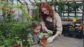 Pretty female gardener in apron and her cute child are stirring soil in pot growing plant in width=