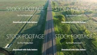 4K aerial footage of a car trucks buses riding on a road between green fields in the sun rise