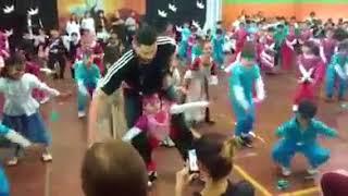 Profesor de Educación Física ayuda a bailar a una nena
