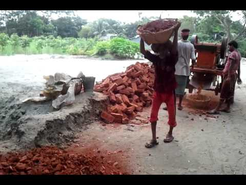 Road workers breaking bricks with a machine in Bangladesh