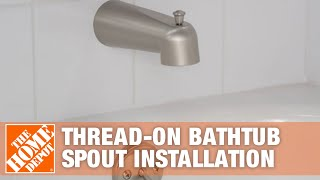 A bathtub faucet and handle installed in a bathroom wall over a tub.