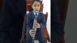 Criança tocando e cantando hino CCB