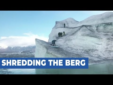 Guy Rides Paddle board Down Side of Iceberg