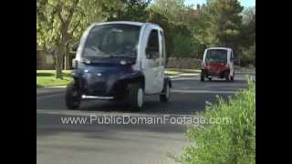 Two electric cars driving down street stock footage